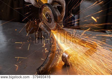 Close-up On The Sides Fly Bright Sparks From The Angle Grinder Machine. A Young Male Welder In A Blu