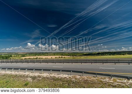 White Traces Of Condensation Of Water Vapor In The Form Of Lines From Flying Planes Over The Highway