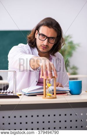 Young male physicist teacher in time management concept