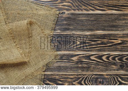 Copy Space On A Rustic Textured Wood Tabletop Painted With Black Paint And Burlap Of Natural Color O