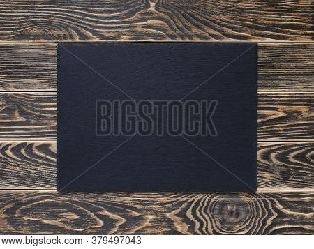 Copy Space On A Black Stone Serving Board Over A Rustic Textured Wood Tabletop Painted With Black Pa