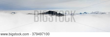 Winter Panoramic View To Snow Covered Mountains Above The Clouds Of Inversion Fog. View From Riedber