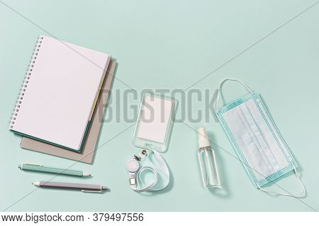School Accessories, New Normal Concept, Face Medical Mask And Hand Sanitizer On Neo Mint Colored Pap