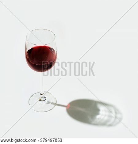 One Glass Of Red Wine On Light Background With Hard Shadow And Copy Space. Wine Bar, Winery, Degusta
