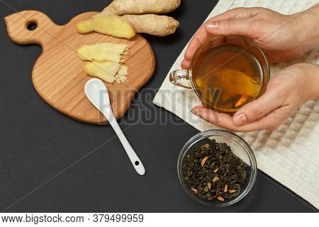 Health Remedy Foods For Cold And Flu Relief. Female Hand With A Cup Of Tea And Ginger On A Wooden Cu