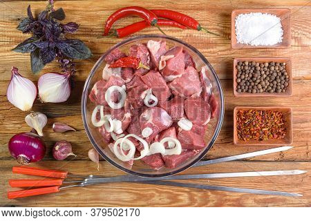 Cooking Kebabs.boneless Lamb Steak, Cut Into Chunks, Meat In A Glass Bowl. Onion, Garlic, Pepper, Ba