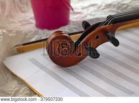 Closeup Scroll Of Violin Put On Background,part Of Acoustic Instrument,blurry Light Around