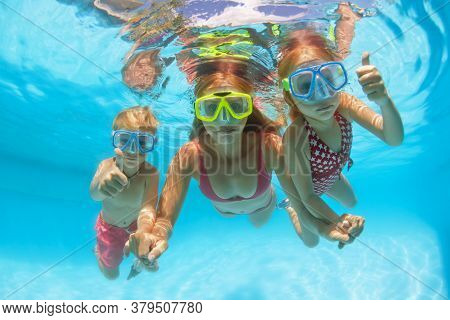 Happy People Dive Underwater With Fun. Funny Photo Of Mother, Kids In Snorkeling Masks In Aqua Park