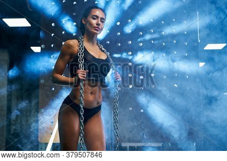 Portrait Of Young Athlete Female With Perfect Muscular Body Posing In Gym, Blue Lights And Smoke On