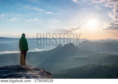 Motivation And Inspiration In Beautiful Sunset Landscape. Female Hiker With Hands In Pocket  On Moun