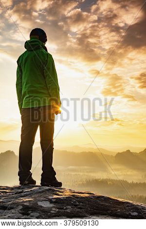 Young Woman Climb The Top In The Mist At Dawn On The Mountain Top Of