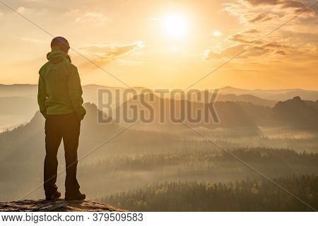 Woman Stands Alone On The Peak Of Rock. Hiker Watching To Autumn Sun At Horizon . Beautiful Moment T