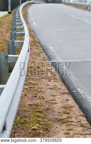 Metal Guardrail Mounted On A Rural Highway Roadside. Vertical Photo