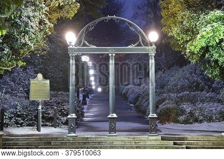 ATHENS, GEORGIA - JANUARY 17, 2018:  The  University of Georgia campus arch with historic state marker in wintertime at twilightl.