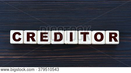 Concept Word Creditor On Cubes On A Beautiful Dark Wooden Background. Business And Finance Concept.