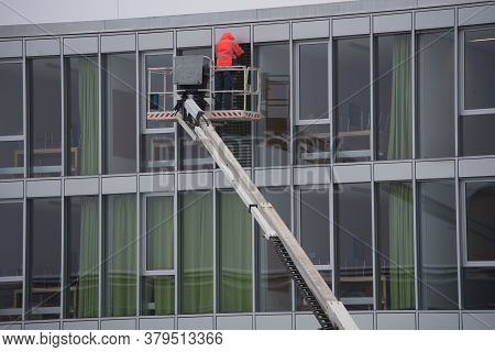 Professional Glazier On A Lifting Platform Mounting A Window On The Outside Of A Building