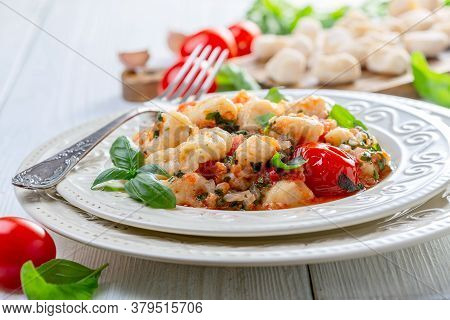 Potato Gnocchi In Tomato Sauce Served In A Plate With Sprig Of Basil On A White Wooden Table, Select