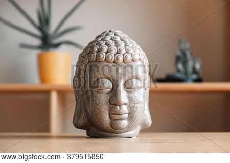 Ceramic Statuette Of A Buddha Head On A Wooden Shelf. Copy, Empty Space For Text