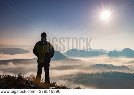 Hiking Man Silhouette Enjoying Amazing Colorful Sunset Mountains. Fantastic Panorama Of Misty And Fo