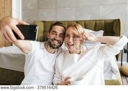 Image of a young happy optimistic loving couple indoors at home taking a selfie by mobile phone showing peace gesture