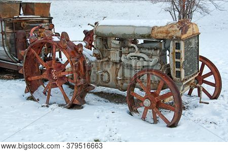 Rusty Antique Farm Tractor In Snow In This Rural Scene.  Tractor Has A Wooden Trailer Attached To Th