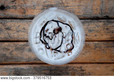 Top View Of Plastic Cup Of Iced Fresh Milk With Chocolate Sauce On Wooden Table.