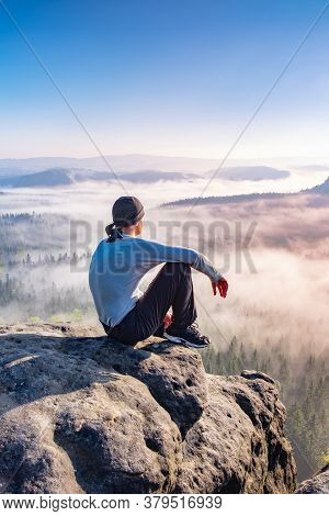 Lone Person Sit Looks Onwards At A Mountain Shrouded In Mist And Clouds With The Peak Visible. Sceni