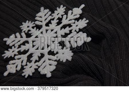 White Snowflake On The Grey Textile Surface In The Upper Right Corner, Free Space For Text. Element