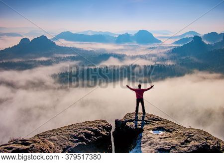 Small Silhouette Of Hiker Man Enjoying Beautiful Sunrise In Morning Mountains. Traveler With Raised