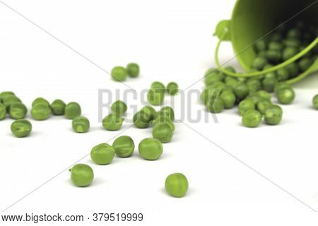 Overturned Green Bucket With Green Peas Scattered On A White Surface