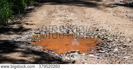 Orange Puddle Soiled With Iron From The Ground. Mountain Dirt Road.