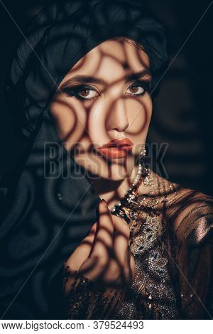 Oriental fairy tale. Portrait of a beautiful arab woman with traditional make-up and black hijab. Make-up and cosmetics.