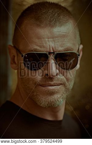 Close up portrait of a handsome brutal mature man with short hair and bristles wearing trendy sunglasses. Manly style. Optics for men.