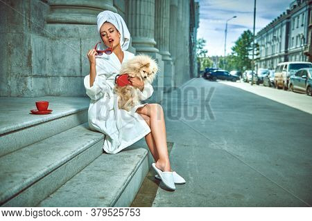 Glamorous lifestyle. Stunning woman in a white terry dressing gown with a white towel on her head and elegant sunglasses posing on a city street with a cup of tea with spitz . Fashion shot.