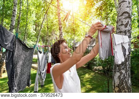 Candid Real Life Portrait Of Young Adult Beautiful Attractive Caucasian Woman Hanging Up Fresh Washe
