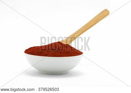 Porcelain Bowl With Paprika Powder Texture With Wooden Spoon On White Background.