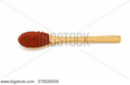 Detail Of Paprika Powder Texture In Wooden Spoon On White Background.