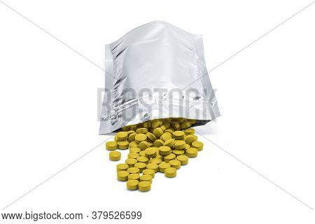 Medicine Tablets, Vitamins And Food Supplements Of Yellow Color In A Resealable Aluminum Bag On Whit