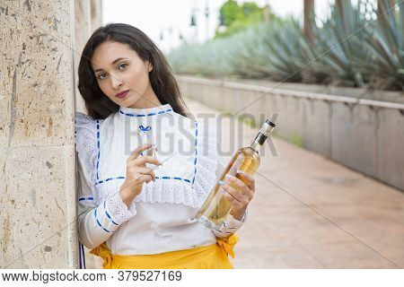Mexican Folk Dancer Drinking Tequila In A Landscape Of Tequila, Mexico