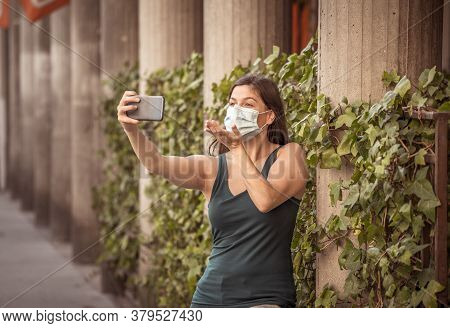 Covid-19 Outbreak. Young Woman Walking In City Street Wearing Protective Surgical Face Mask And Usin