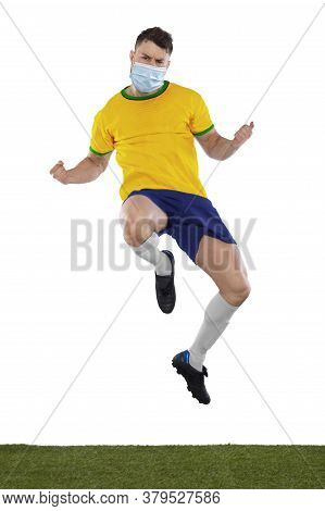 Young Soccer Player On Grass With Yellow Shirt And Mask In Face On White Background