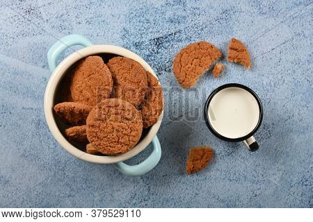 Close Up Round Artisan Oatmeal Cookies And Pannikin Mug Of Milk On Blue Painted Rustic Wooden Table,