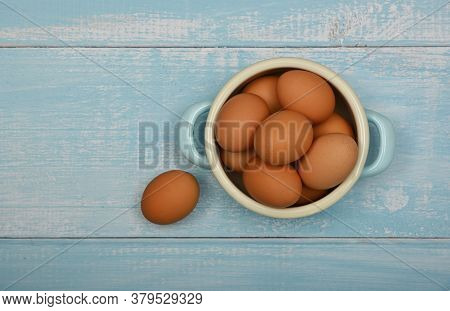 Close Up Metal Pan Bowl Of Brown Chicken Eggs On Light Blue Rustic Wooden Table Surface, Elevated To