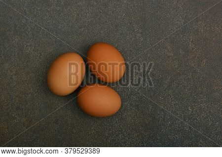 Close Up Three Brown Chicken Eggs On Dark Grunge Table Surface, Elevated Top View, Directly Above