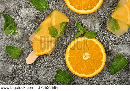 Close Up Two Fruit Ice Cream Popsicles With Fresh Orange Slices, Green Mint Leaves And Ice Cubes On
