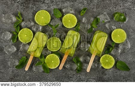Close Up Several Frozen Fruit Juice Popsicles With Fresh Lime Slices, Green Mint Leaves And Ice Cube