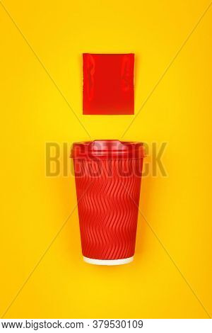 Close Up One Crimped Disposable Red Paper Takeaway Cup And Instant Coffee, Sugar Or Teabag Sachet Ov