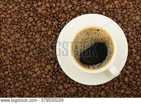Close Up White Cup On Saucer Full Of Black Coffee Over Background Of Roasted Coffee Beans, Elevated