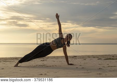 Side View Of Young Woman Working Out On The Beach In The Morning, Holding A Side Plank Position