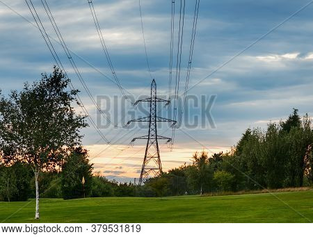 Power Line And Electrical Transmission Tower Or Electricity Pylon Or Power Tower On Field.